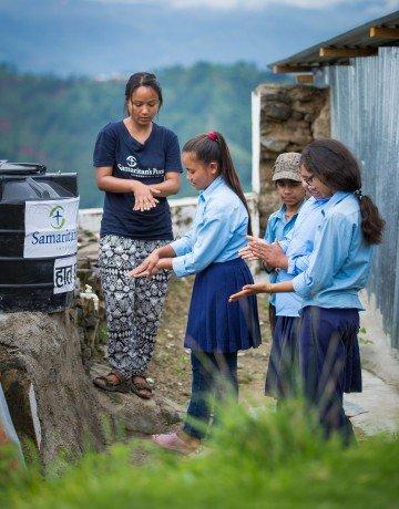 Staff member Sujana Lama teaches hand-washing techniques to schoolchildren.