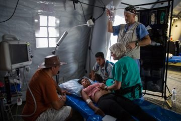 Monica receives an exam at the emergency field hospital