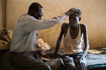 Pastor Andrea Aja prays over a patient.