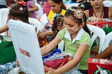 A child of one of the patients at the Samaritan's Purse emergency field hospital smiles as she opens her shoebox gift. Samaritan's Purse and local ministry partners held an Operation Christmas Child outreach event on June 1, International Children's Day, for 580 children.