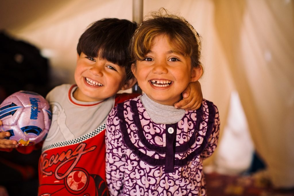 Ala's older two children play together in the family's makeshift home.