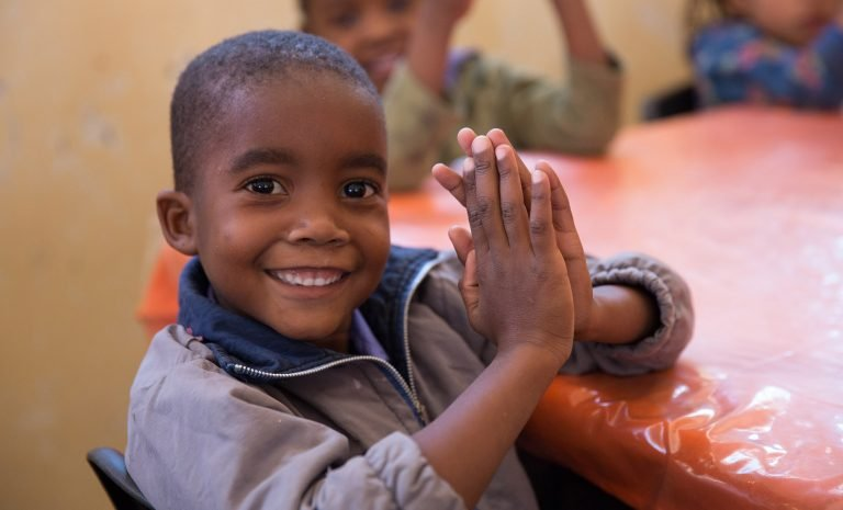 Young boy praying in Nambia at OCC event