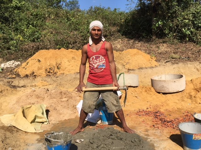A Rohingyan man mixes cement for the construction of latrines for the new clinic.