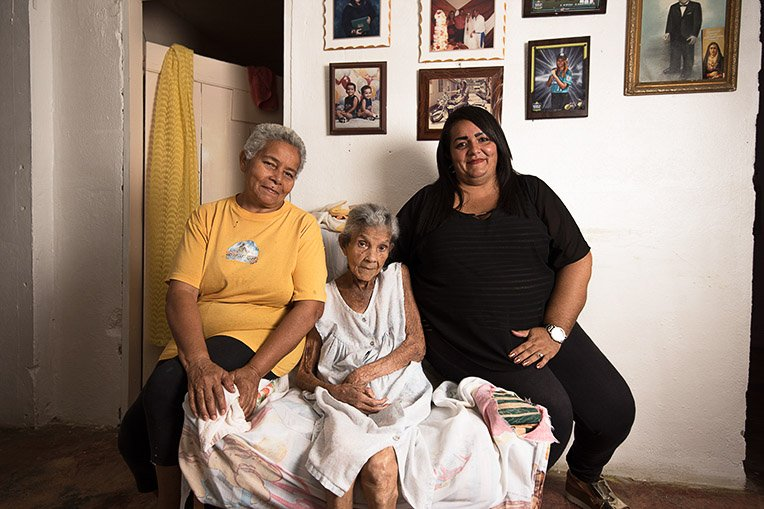 Cecilia Burgos, center, was the first to receive a solar energy relief system at her home. She is joined by daughter Maria Burgos, left, and granddaughter Cecilia Martinez.