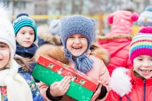 Child smiling with red and green shoebox gift