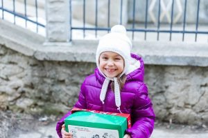 Child in white hat and purple coat smiling with red and green shoebox gift
