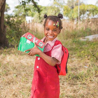 Thumbnail - little girl in red dress holding shoebox gift