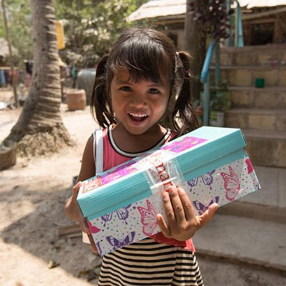 Smiling girl holding butterfly shoebox