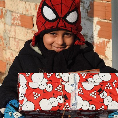 Boy in spiderman hat with red shoebox