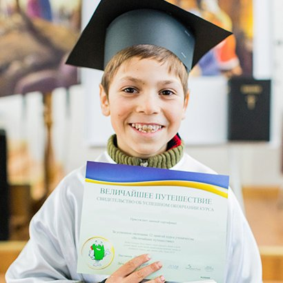 The Greatest Journey - boy at graduation with certificate and New Testament Bible