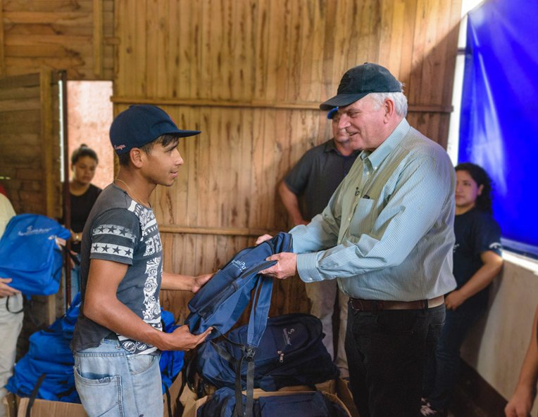 Franklin Graham helps distribute Samaritan's Purse backpacks filled with daily essentials.