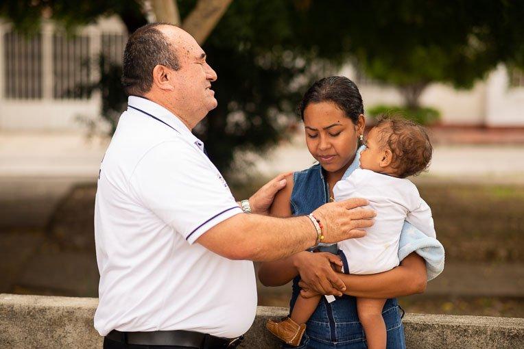 Jairo Antonio Garson Lopez, centre coordinator, prays with Orangeles and her son.