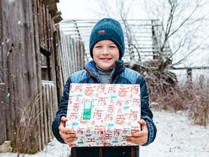 Boy in the snow with shoebox gift