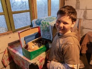 Boy explores shoebox gift in home