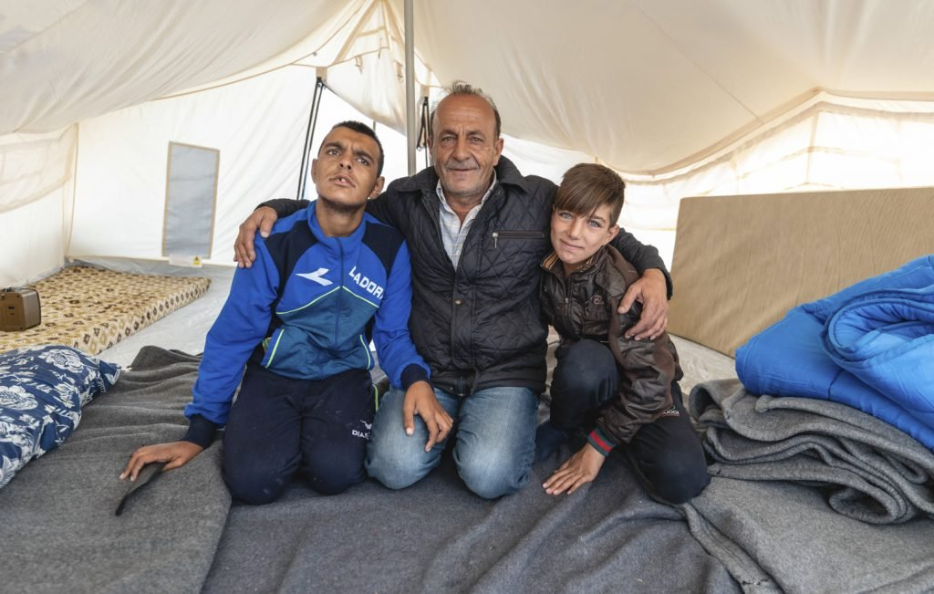 Diyar (center) and his two sons find refuge in their tent.