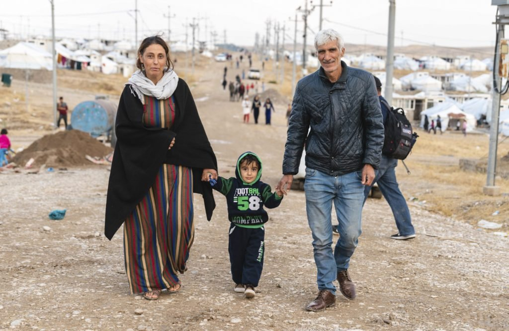 Mirko and his wife and young son walk down the road in Bardarash camp.