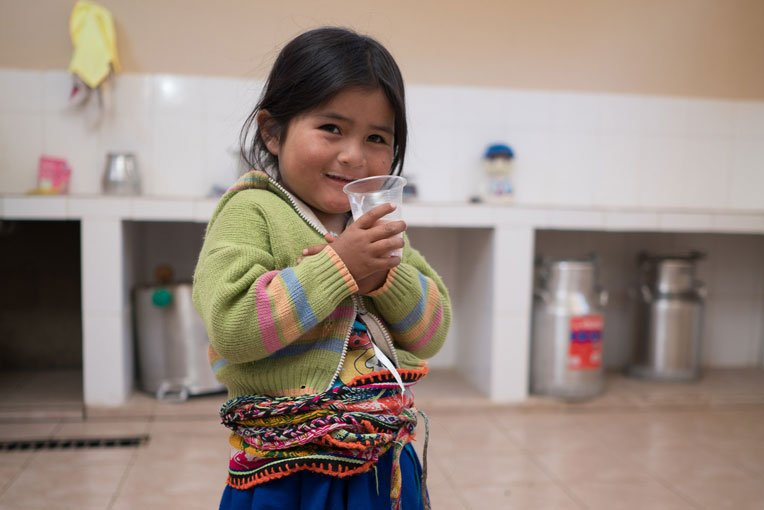 A child enjoys freshly pasteurised milk at the dairy processing centre.