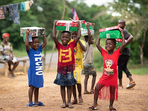 group of children holding shoeboxes above head