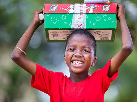 Boy in red holds shoebox high
