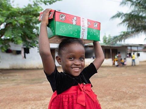 Little girl holds shoebox on head