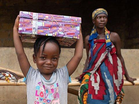Girl holds shoebox above head