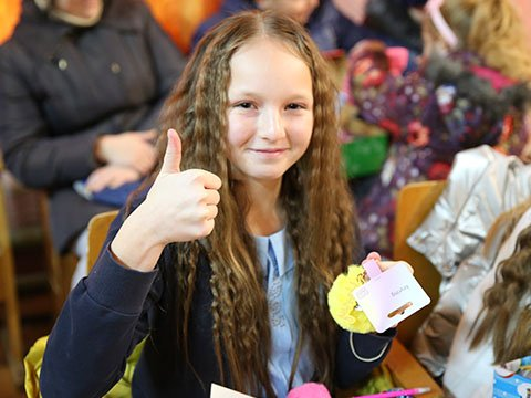 Girl gives thumbs up to her shoebox gift