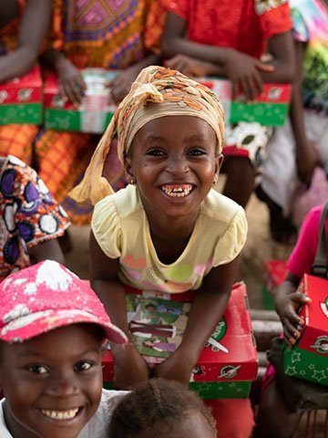 Girl in hat with shoebox smiles