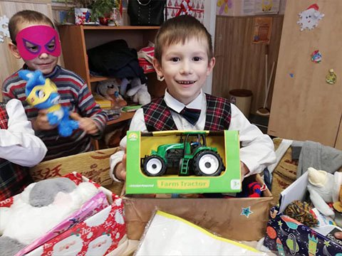 Boy shows off tractor from shoebox