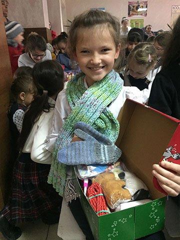 girl smiles with open shoebox