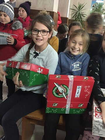 two girls with shoebox gifts
