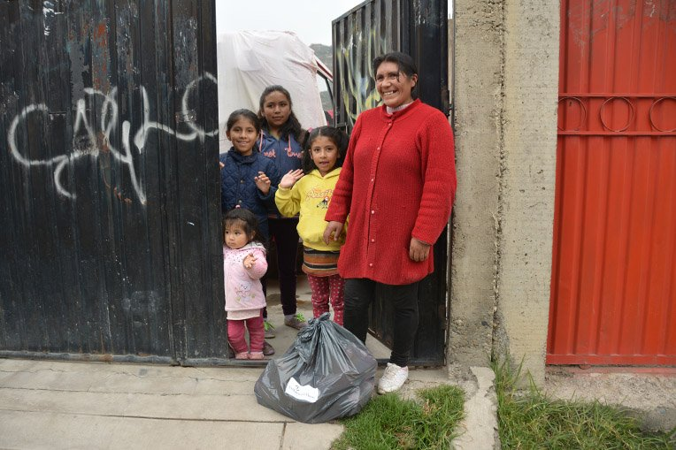 A family greets our Samaritan's Purse team in Bolivia as they deliver a bag of food supplies to their home.