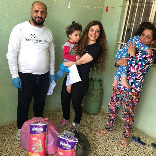 Sandra (right) receives food and hygiene kits from Samaritan's Purse staff.