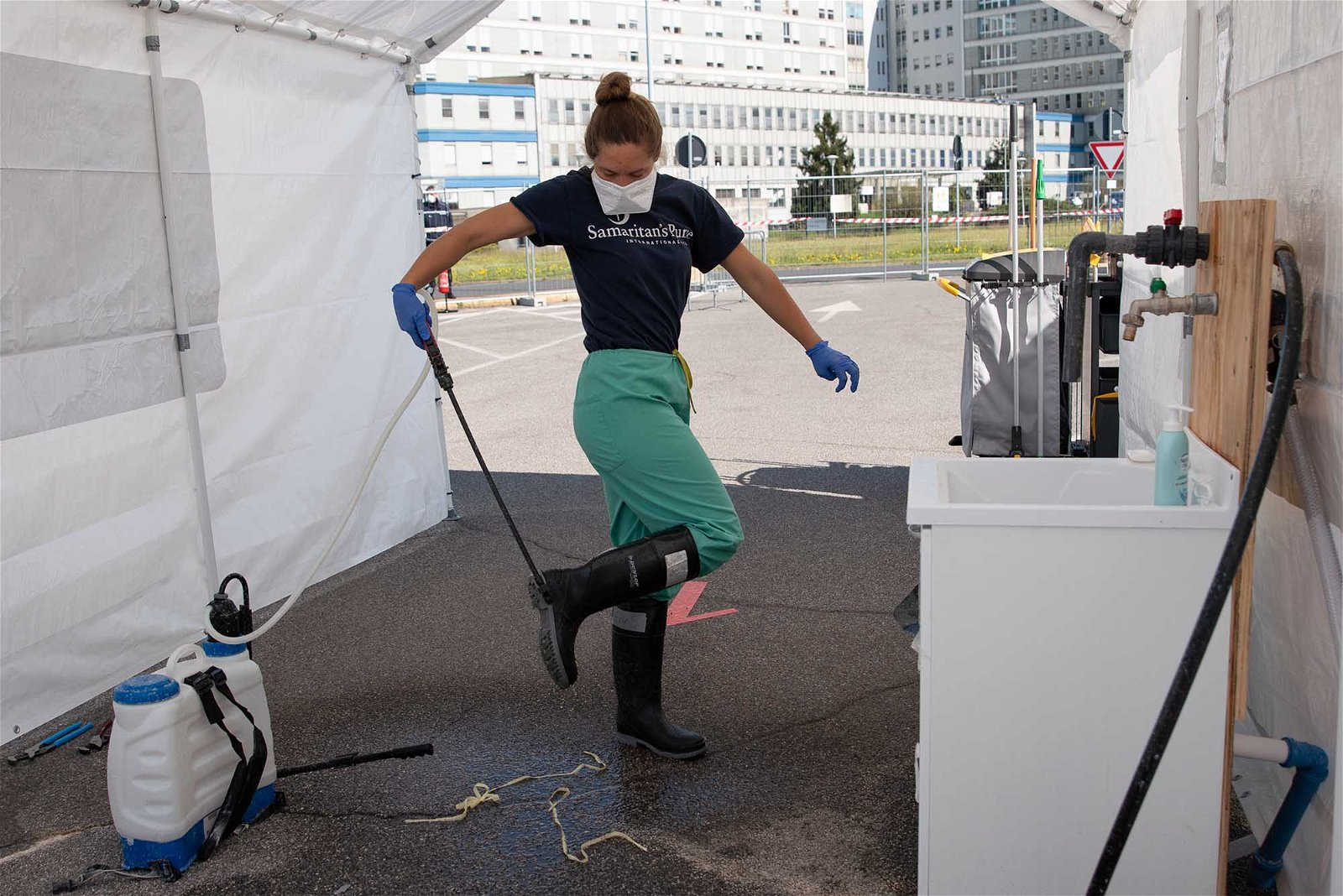 Erin, a nurse, decontaminates her boots with a chlorine solution on her way out of the hot zone.