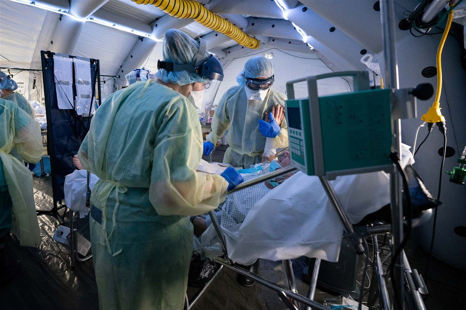 Dr. Bob, right, speaks with and comforts an improving patient in the ICU at the SP field hospital for coronavirus patients in Cremona, Italy.
