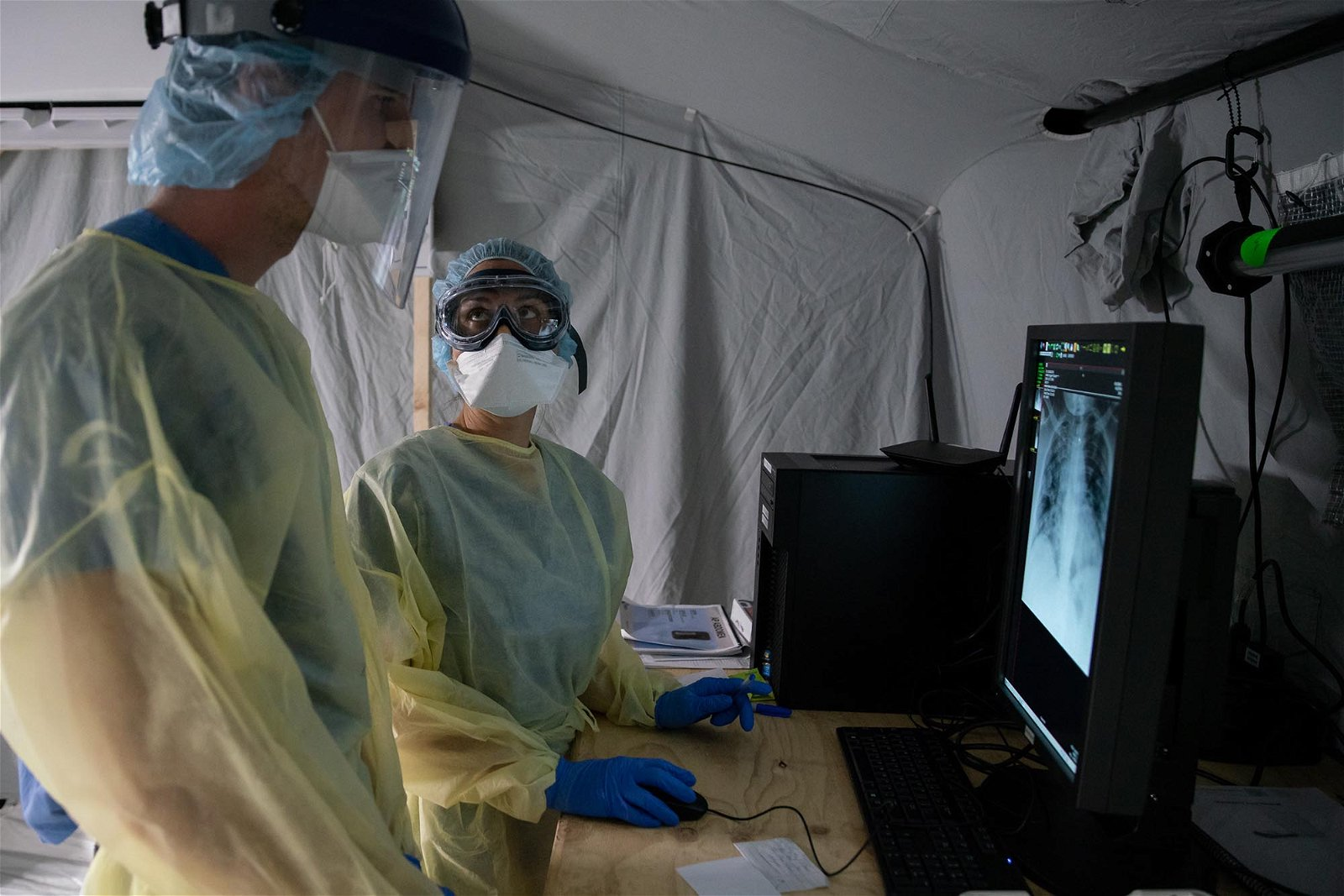 Stephanie, a physician's assistant, reviews patient x-rays with Lucca, a translator who is in medical school, as she orients him to the SP field hospital in Cremona.