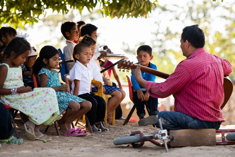 PASTOR JOSÉ BENÍTEZ LEADS CHILDREN IN SONG AND PRAYER IN LA LAGUNA DURING THEIR GRADUATION FROM THE GREATEST JOURNEY.