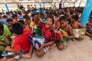 Children are excited to show off their shoebox gifts during a well-attended outreach event.