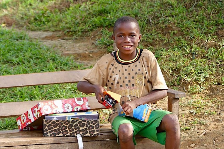 A BOY FROM VANYANPA ENJOYS UNPACKING HIS SHOEBOX GIFT.