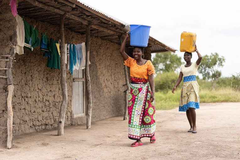 Eunice and her daughter carry water back to their home.