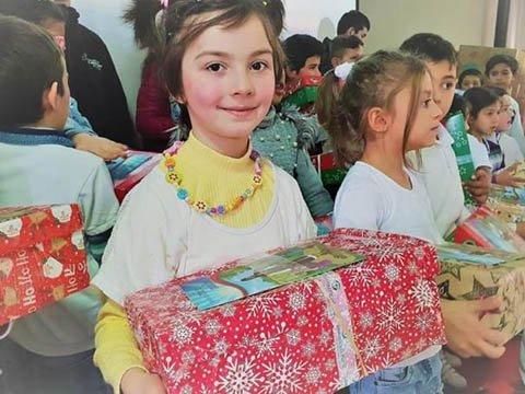 Girl smiles with shoebox gift