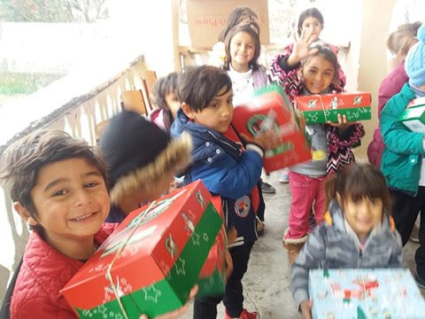 Group of children smile and wave with shoeboxes