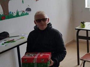 Boy in sunglasses holds shoebox