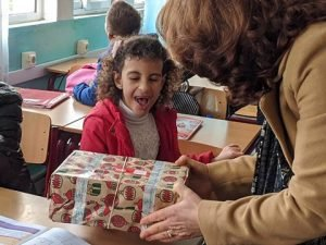 delighted girl reacts to shoebox gift with excitement