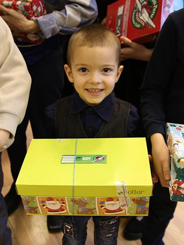 little boy smiles with yellow shoebox