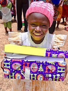 girl grins with shoebox gift