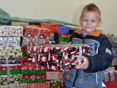 boy smiles with shoebox gift in front of pile of boxes
