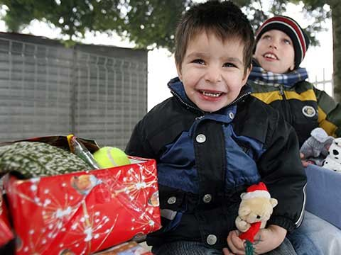 boy outside smiles with red shoebox