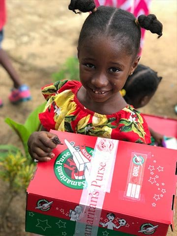 Girl in Liberia smiles with shoebox gift
