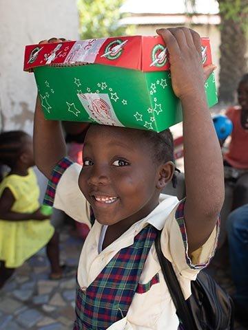 girl holds shoebox on head