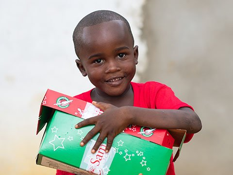 Young boy with red and green shoebox